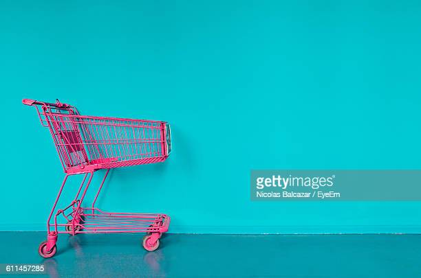 pink shopping cart against turquoise wall - shopping cart stock pictures, royalty-free photos & images