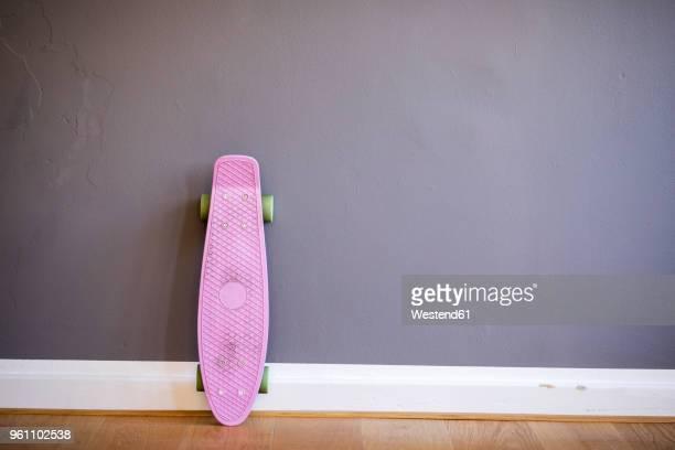 pink skateboard leaning against wall - skate fotografías e imágenes de stock