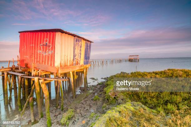 Pink sky at dawn on the Palafito Pier in the Carrasqueira Natural Reserve of Sado River, Alcacer do Sal, Setubal, Portugal, Europe