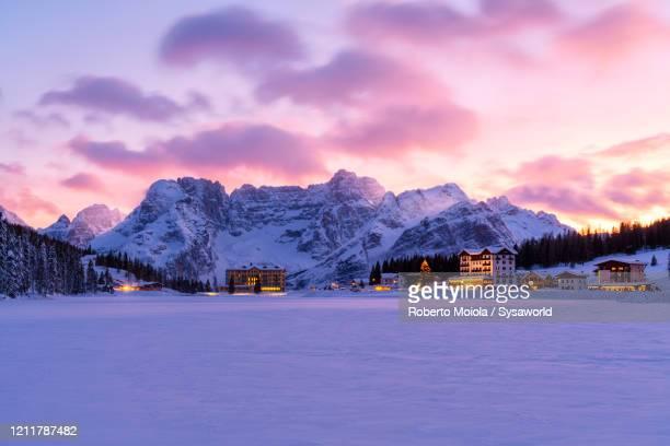 pink sky at sunset on misurina and sorapis covered with snow, dolomites, veneto, italy - 冠雪 ストックフォトと画像