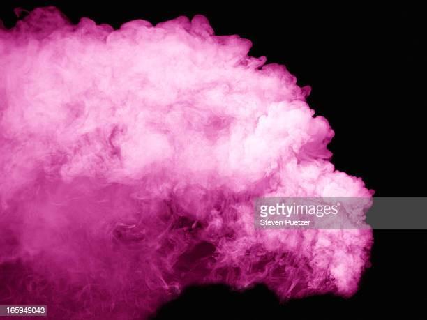 Pink smoke against black background