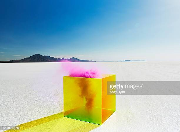 Pink smoke escaping yellow box on salt flats.