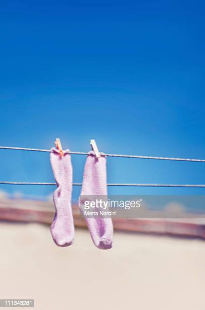Pink socks drying on line over the blue sky