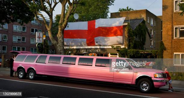 Pink stretch limousine parked outside a George flag displayed in the entrance to the Victory pub on the 2nd June 2006 in Camden, London, United...