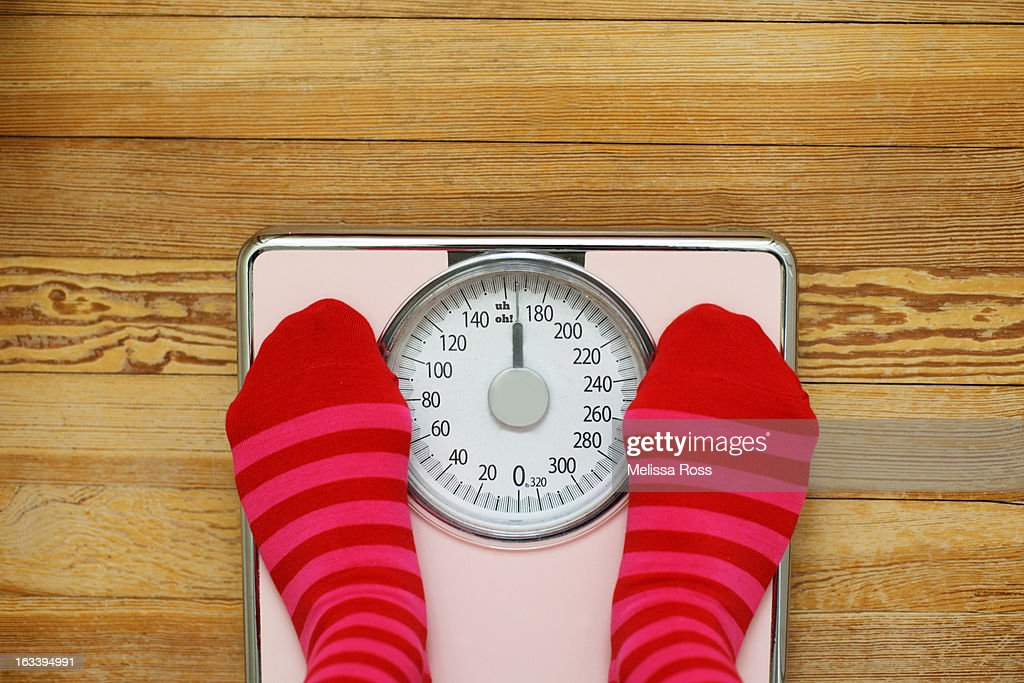 Pink striped socks standing on pink scale : Stock Photo