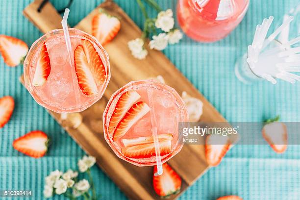Pink summer cocktail drink from above with strawberries