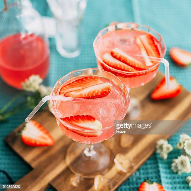 Pink summer cocktail drink with strawberries