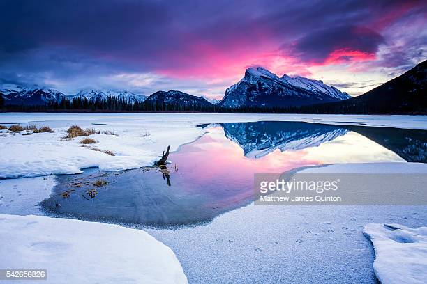 Pink sunrise over mountain reflected in partially frozen lake with snow