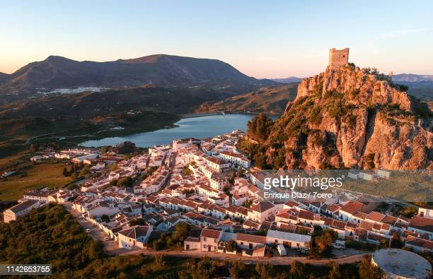 pink sunset cast over zahara de la sierra, andalusia, spain - andalusia stock pictures, royalty-free photos & images