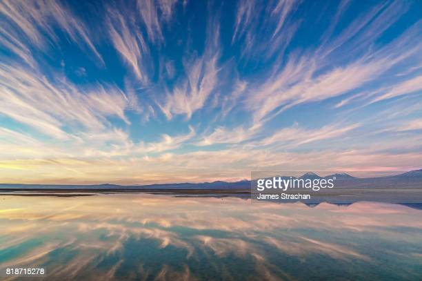 Pink sunset over and reflected in Laguna Chaxa, Atacama Salt Flats, with snow-capped volcanoes in thebackground, near San Pedro de Atacama, Chile