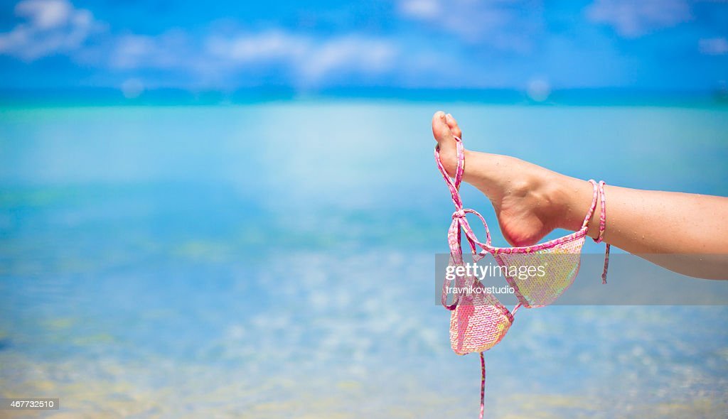 Pink swimsuit on female leg on white tropical beach