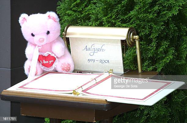 A pink teddy bear sits beside the guest book for deceased RB singer Aaliyah August 30 2001 at the Frank E Campbell funeral home in New York City on...