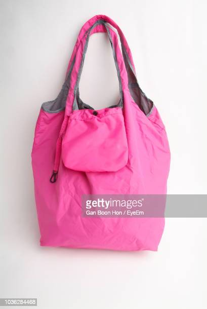 pink tote bag hanging on white wall - トートバッグ ストックフォトと画像