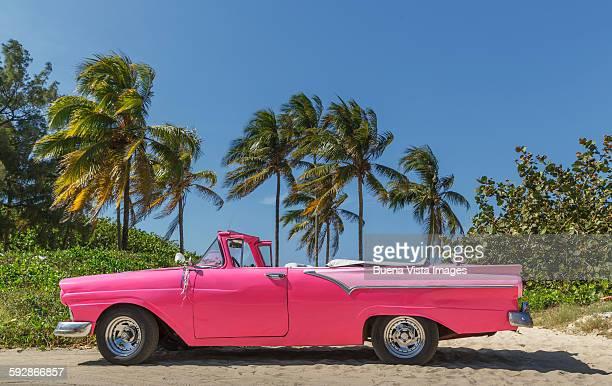 Pink vintage car on a cuban beach.