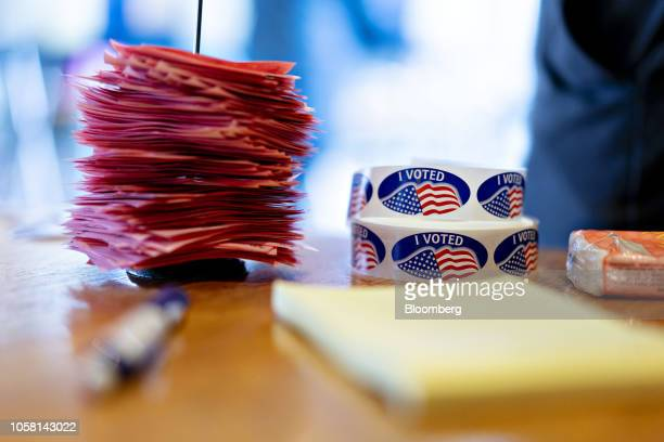"""Pink voter count slips sit in a stack next to """"I Voted"""" stickers at a polling station inside the clubhouse at Currie Park Golf Course in Wauwatosa,..."""