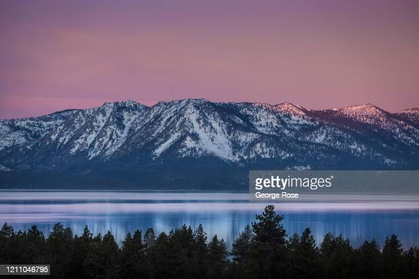 Pinkish color lights the sky over the mountains before sunrise on March 5 in South Lake Tahoe, California. After a series of heavy snowstorms in...