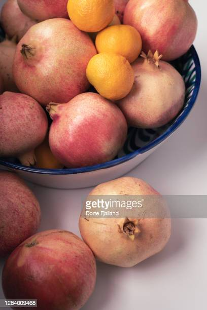 pinkish pomegranates and mandarines on a white table - dorte fjalland stock pictures, royalty-free photos & images