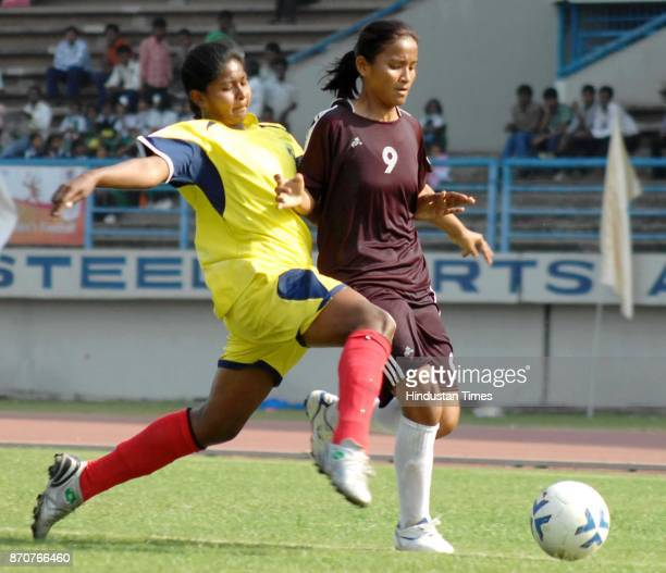 Pinky Bompal Magar of Odisha and Nagi Mardi captian of Jharkhand fighting for ball during women footbal event of 34th National Games at J R D Tata...