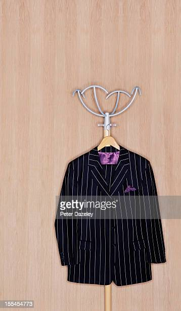 pinstripe suit hanging against a wooden background - striped suit stock pictures, royalty-free photos & images