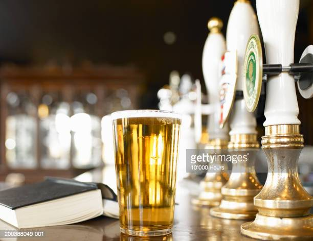 Pint of beer and book on bar