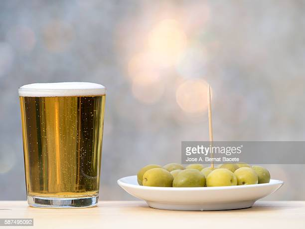 Pint of beer and bowl of green olives on a wooden table outside, lit by sunlight