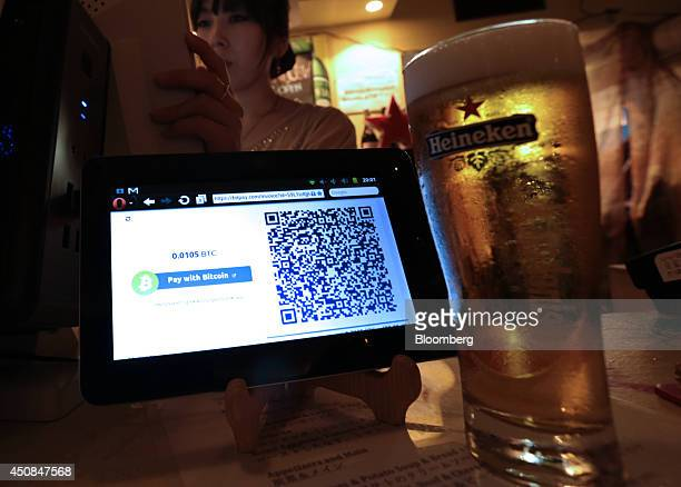 A pint of beer in a Heinekenbranded glass purchased with bitcoin sits on a counter beside a cash register at The Pink Cow restaurant and bar in Tokyo...