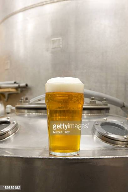 a pint of beer with brewery tanks in backround - the brewery london stock photos and pictures