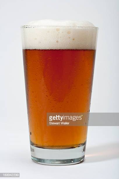 pint of frothy beer - ale stock pictures, royalty-free photos & images