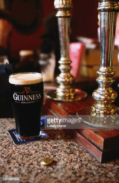 Pint of Guinness on bar in pub.