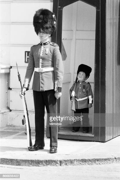 Pint sized soldier Mark Acklom aged 3 from Greenways Beckenham Kent wearing a miniature guards outfit complete with rifle stands guard outside...