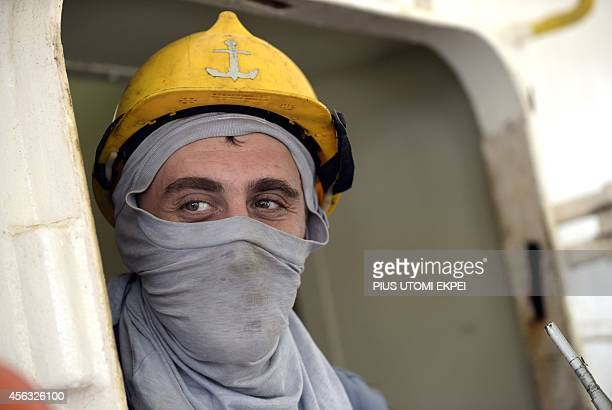 MV Pintail Ukrainian sailor Levgeny Sarayev uses a Tshirt to make a face mask as Nigerian health workers onboard check for signs of the Ebola virus...