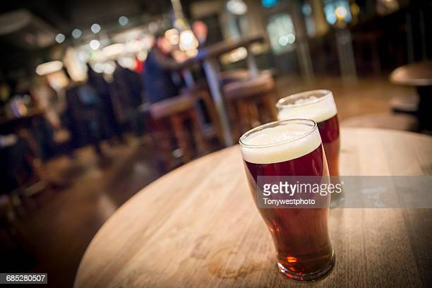 pints of ale in a pub in the city of london - ale stock pictures, royalty-free photos & images