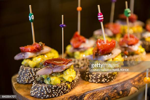 Pintxos tapas with cocktail sticks on wooden cutting board. Bilbao, Spain