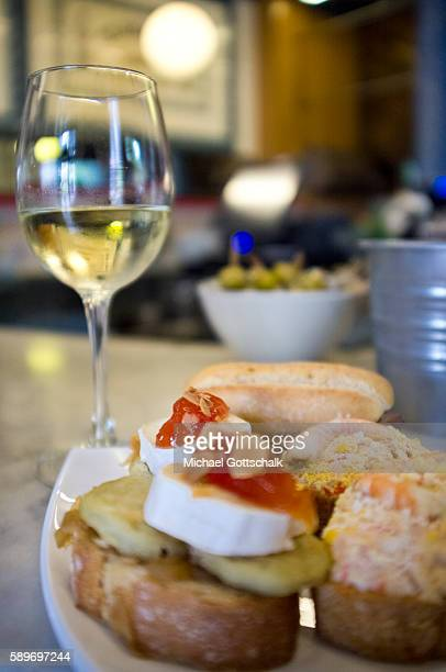Pintxos typical nordspanish slices of bread with different toppings next to a plas of vine on May 12 2016 in Bilbao Spain