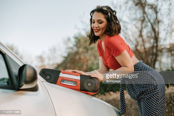 Pin-Up girl listening to music from a radio in the city street