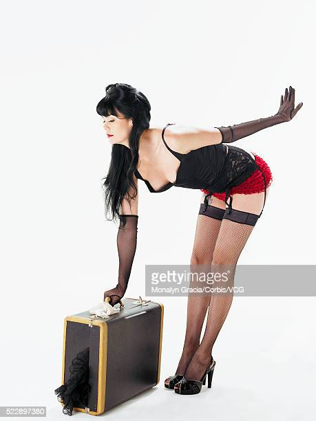 Pinup girl picking up heavy suitcase