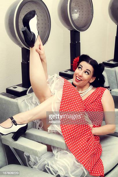 Pin-up girl: sexy woman in a beauty salon with hairdryers