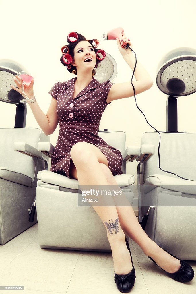 Pin-up girl: sexy woman wearing rollers in a beauty salon : Stock Photo