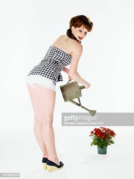 Pinup girl watering potted plant