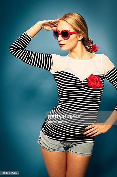 Pin-up girl with red heart shaped sunglasses looking