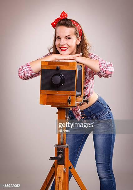 Pin-up-Mädchen mit retro hölzernen Kamera