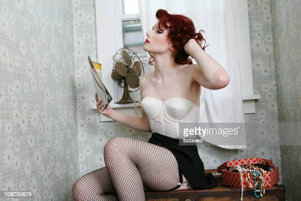 pin-up style retro woman cooling herself off with fan - mini skirt photos stock photos and pictures