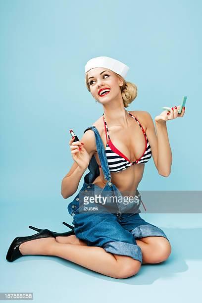 Pin-up-Stil Matrose Frau benutzt Lippenstift.