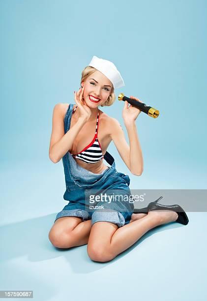 Pin-up-Stil Matrose Frau hält ein Teleskop und Lächeln