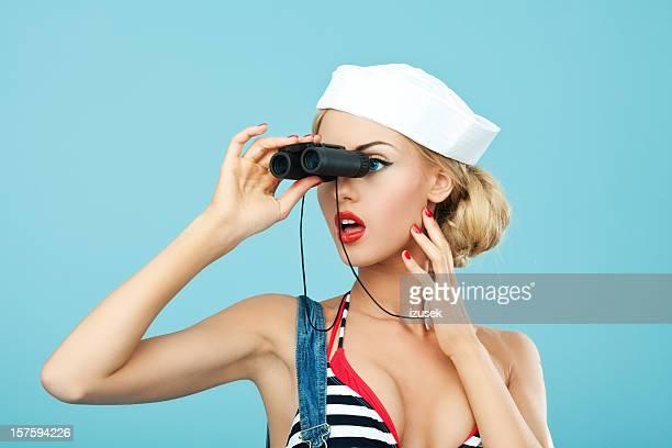 Pin-up style sailor woman looking through binoculars