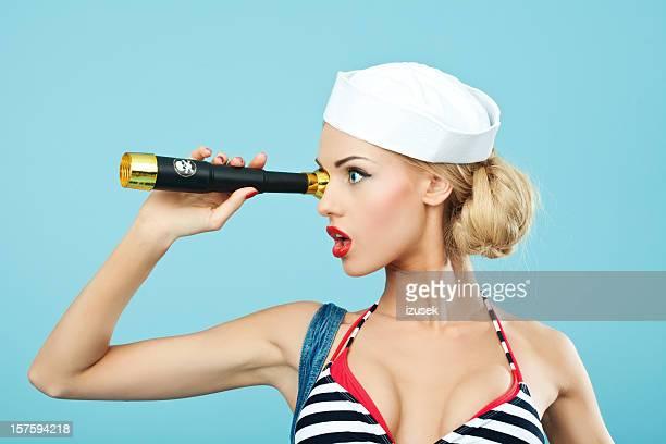 Pin-up estilo mujer mirando a través del telescopio marinero