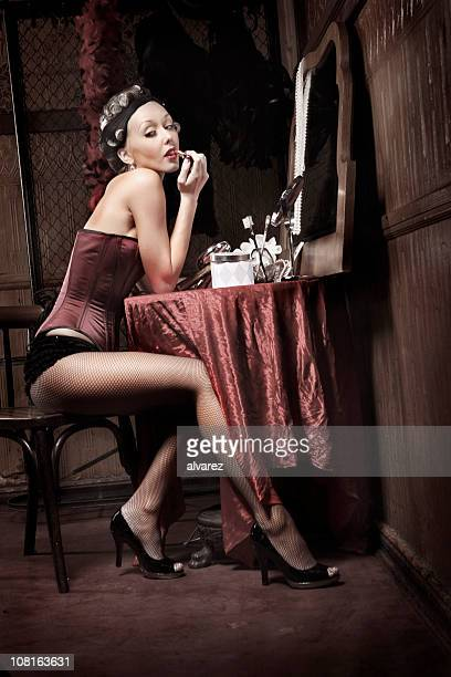 Pin-Up Style Woman Putting on Make-up in Mirror