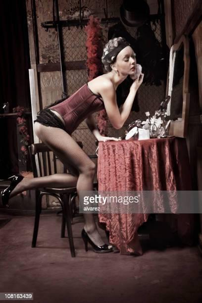 Pin-Up-Frau mit Lockenwickler Powdering Gesicht im Spiegel