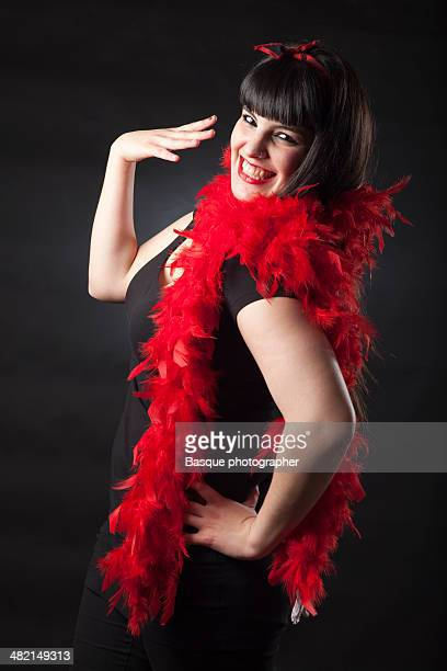 Pin-up woman smiling with red boa in the neck