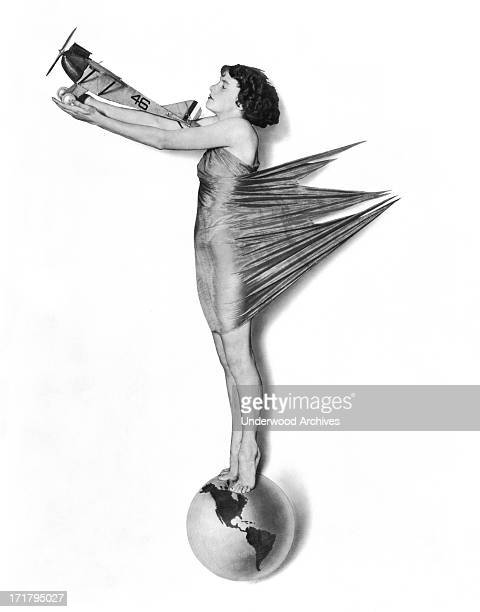 A pinup woman stands on a globe holding a single engine plane in her outstretched arms circa 1927